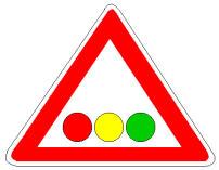 Sinjali në figurë paralajmëron një impiant semaforik, me vendosje horizontale të fenerëve.