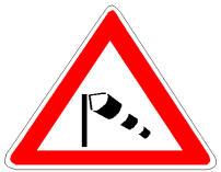 Sinjali në figurë paralajmëron një pjesë rruge, në të cilën krijohen erëra të forta anësore.